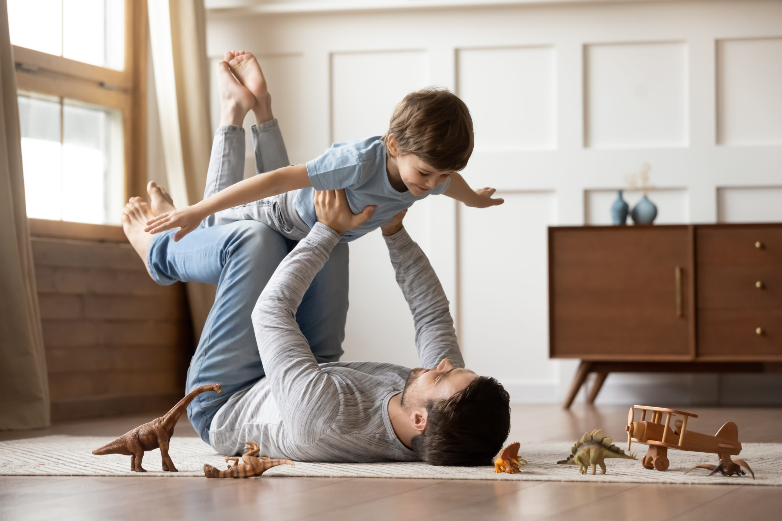 Young father playing at home with preschooler son